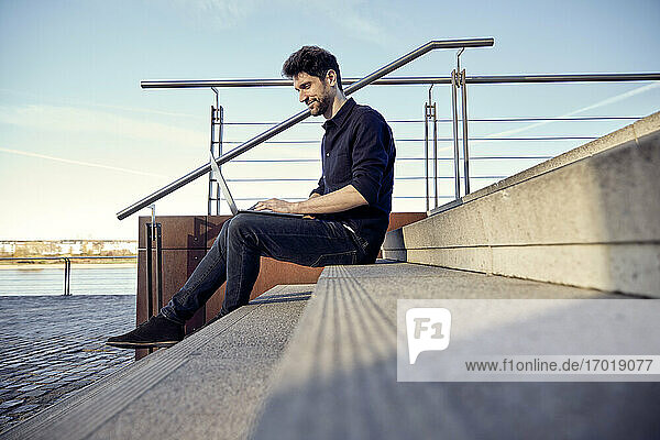 Entrepreneur using laptop while sitting on steps