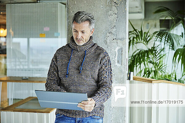 Businessman using digital tablet while standing against pillar at office