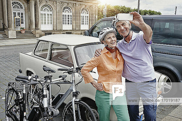 Smiling couple wearing cycling helmet taking selfie Trabant car while standing at Dresden  Germany