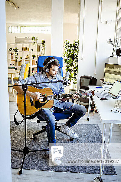 Musician with microphone playing guitar while sitting at recording studio