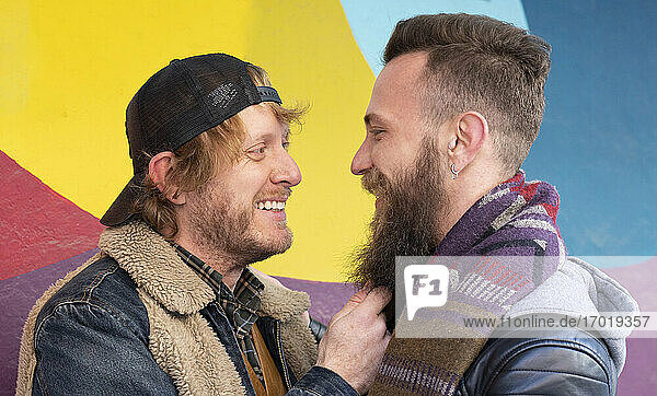 Close-up of smiling gay couple looking at each other against multi colored wall