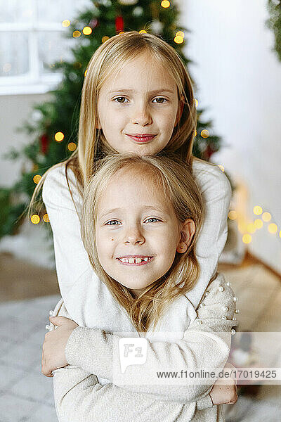 Smiling sisters embracing with Christmas tree in background at home