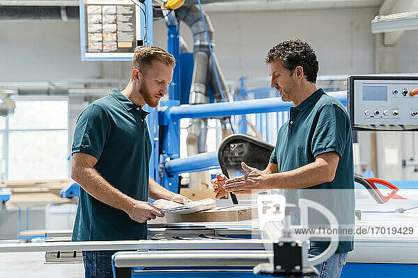 Two male carpenters working together in production hall