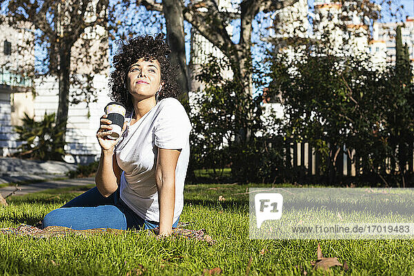 Woman with coffee cup looking away while sitting on grass