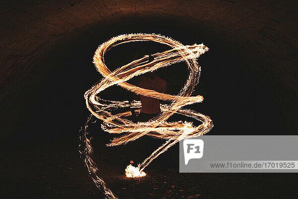 Male fire juggler performing skill in dark tunnel