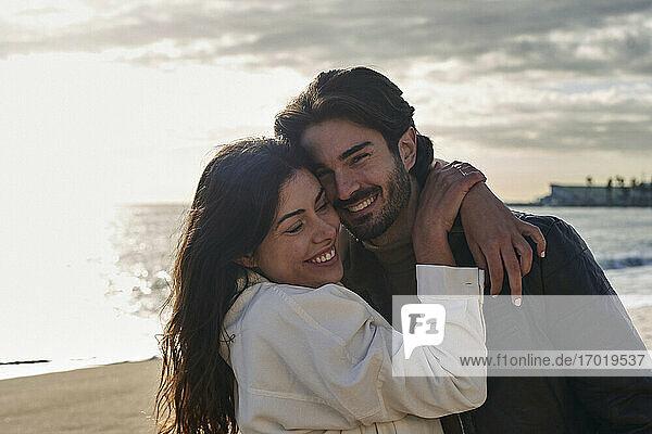 Lächelnde Frau umarmt Mann am Strand stehend