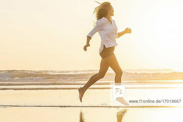 Frau schaut auf das Meer  während sie am Strand bei Sonnenuntergang läuft Frau schaut auf das Meer, während sie am Strand bei Sonnenuntergang läuft