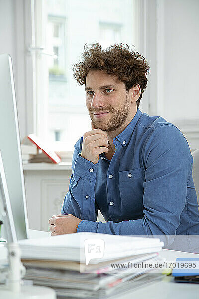 Young businessman with hand on chin working in office