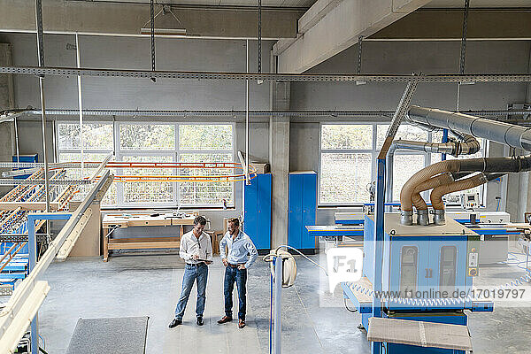 Zwei Zimmerleute stehen und unterhalten sich in einer Produktionshalle