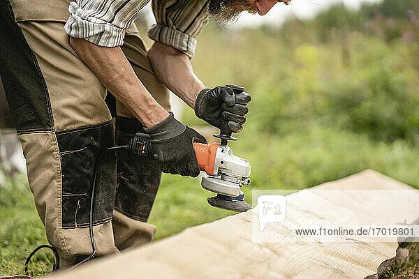 Schreiner schleift Brett mit Handschleifmaschine Schreiner schleift Brett mit Handschleifmaschine
