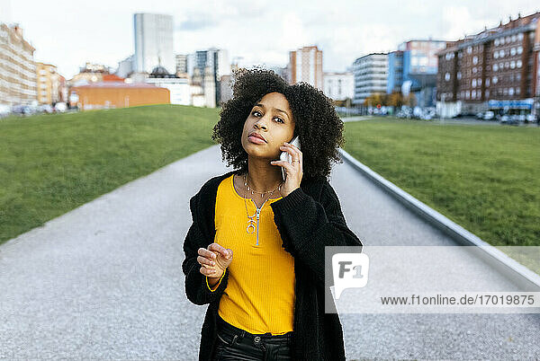 Young woman with afro hair talking over smart phone while standing on footpath in city