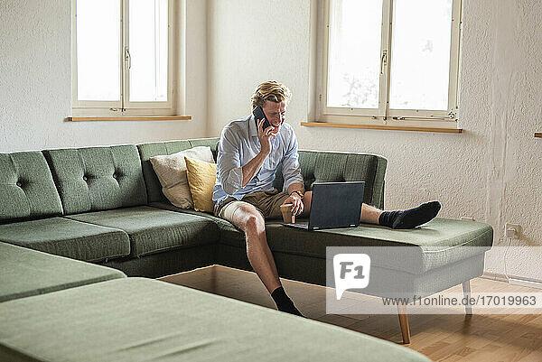 Männlicher Freiberufler bei der Arbeit  während er im Wohnzimmer mit seinem Smartphone telefoniert