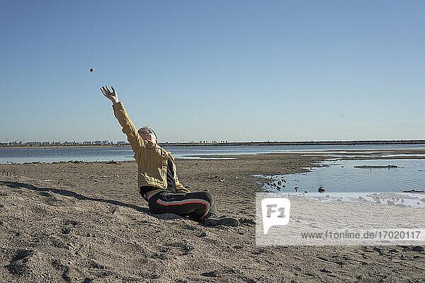 Junge sitzt allein am Sandstrand und wirft Steine Junge sitzt allein am Sandstrand und wirft Steine