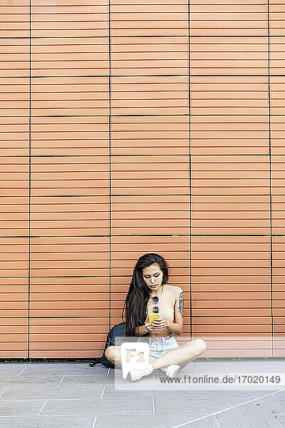 Young woman using mobile phone while sitting against wall