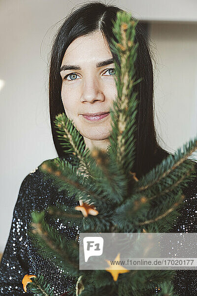 Mid adult woman holding small Christmas tree while standing at home