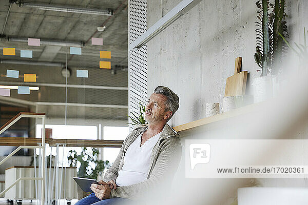 Thoughtful man with digital tablet looking away