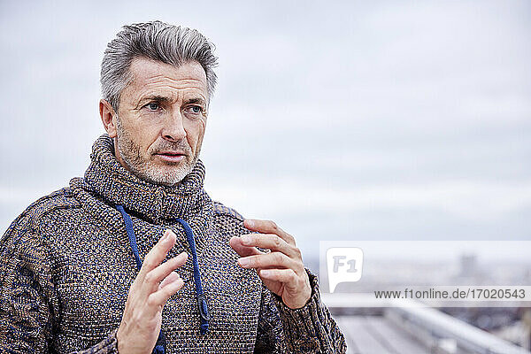 Mature man wearing sweater gesturing while standing against sky