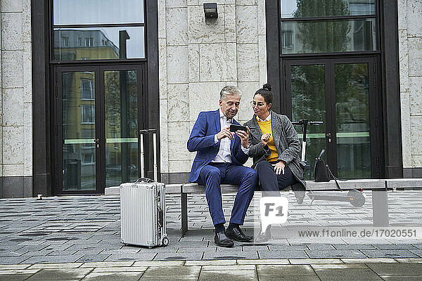 Senior businessman sharing smart phone with female professional while sitting on bench against building