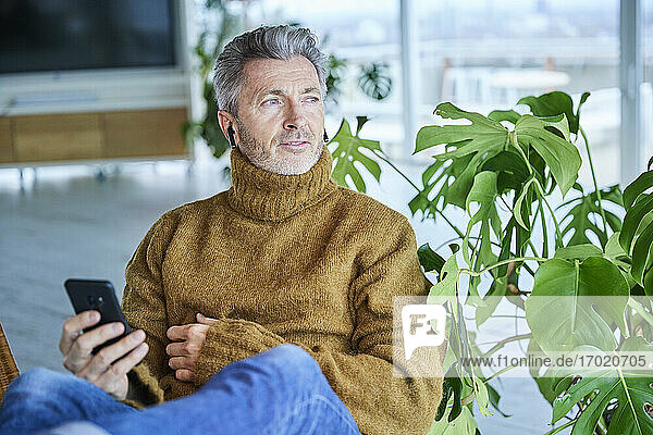 Mature man wearing in-ear headphones using mobile phone while sitting at home