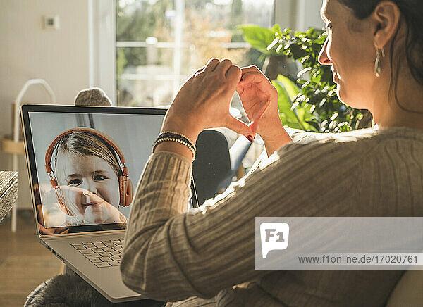 Frau  die während eines Videogesprächs mit einem kleinen Mädchen ein Herz mit den Händen formt Frau, die während eines Videogesprächs mit einem kleinen Mädchen ein Herz mit den Händen formt