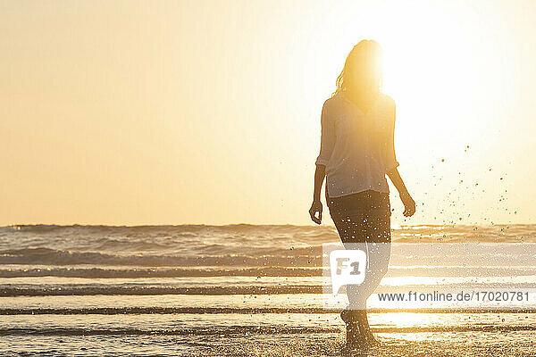 Silhouette einer Frau,  die bei Sonnenuntergang am Strand steht und im Wasser plantscht