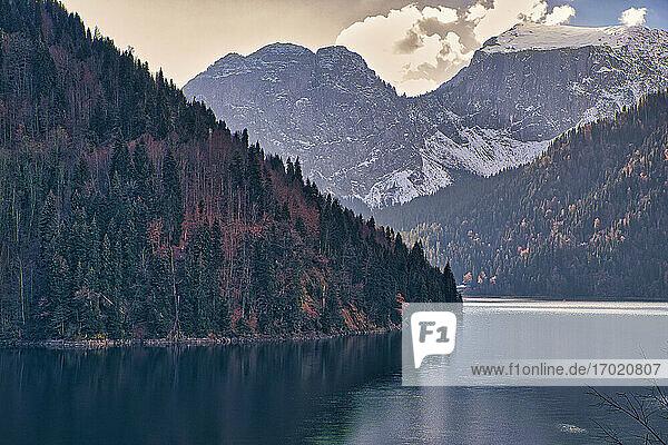 Lake Ritsa surrounded by forested mountains in autumn  Abkhazia  Georgia