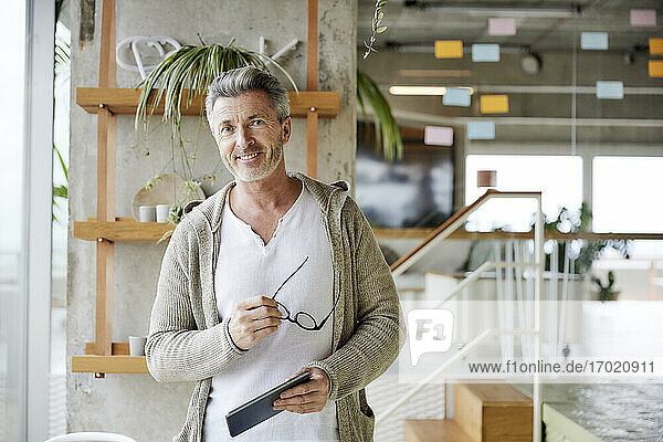 Smiling mature man holding digital tablet and eyes glasses while standing at office