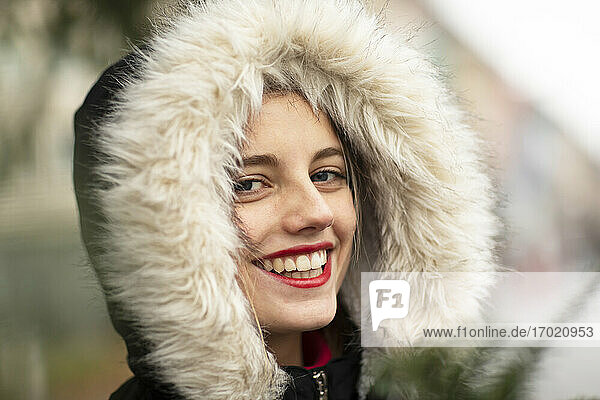 Happy young woman wearing jacket with fur during Christmas