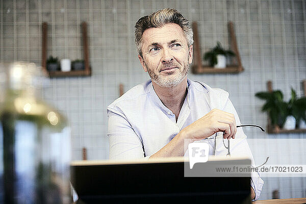 Thoughtful businessman with digital tablet looking away