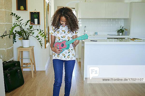 Lächelnde junge Frau spielt Ukulele im Wohnzimmer Lächelnde junge Frau spielt Ukulele im Wohnzimmer