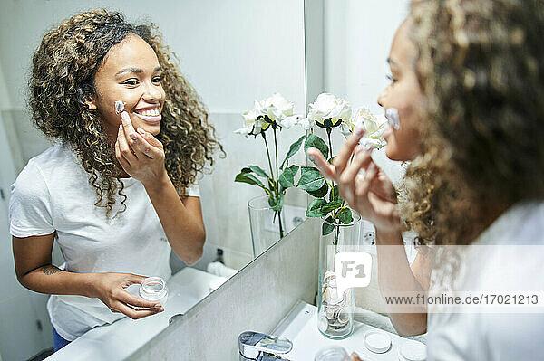 Schöne lächelnde Frau trägt Gesichtscreme auf und betrachtet ihr Spiegelbild im Badezimmer Schöne lächelnde Frau trägt Gesichtscreme auf und betrachtet ihr Spiegelbild im Badezimmer