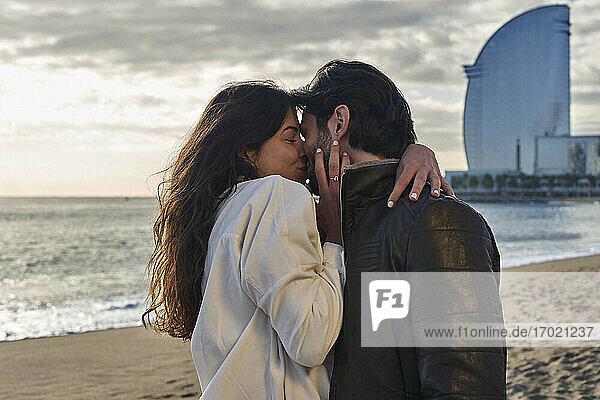 Freundin mit Arm um Freund küssend am Strand stehend
