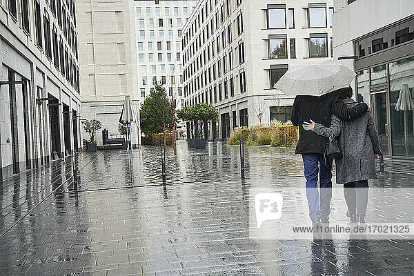 Businesswoman and senior businessman with arms around walking under umbrella in city during rainy season