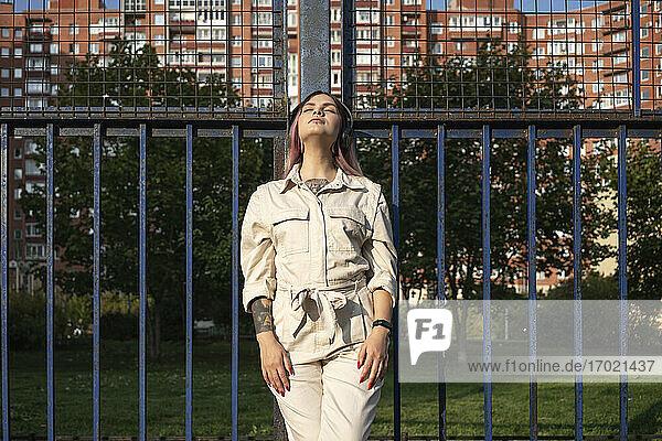 Modische junge Frau mit geschlossenen Augen am Zaun an einem sonnigen Tag Modische junge Frau mit geschlossenen Augen am Zaun an einem sonnigen Tag