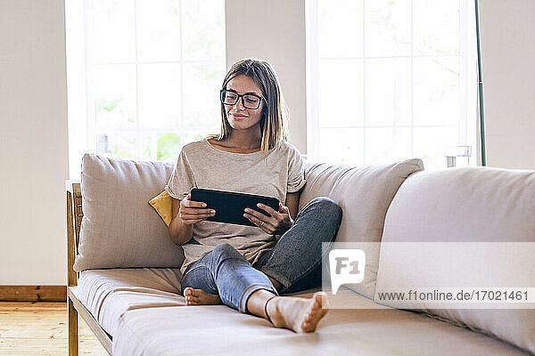 Entspannte brünette Geschäftsfrau  die auf dem Sofa sitzt und ein digitales Tablet im Wohnzimmer zu Hause benutzt Entspannte brünette Geschäftsfrau, die auf dem Sofa sitzt und ein digitales Tablet im Wohnzimmer zu Hause benutzt