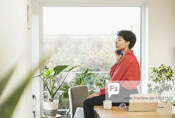 Frau benutzt Smartphone am Tisch mit Laptop zu Hause Frau benutzt Smartphone am Tisch mit Laptop zu Hause