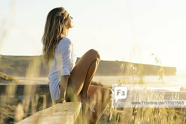 Woman resting while sitting on railing at beach