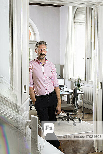 Male professional looking leaning on doorway of office