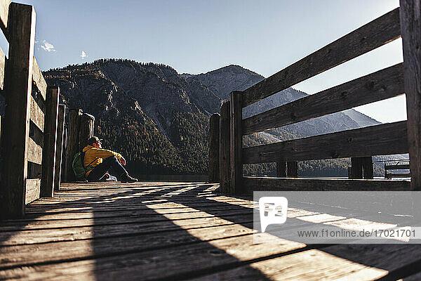Älterer männlicher Wanderer sitzt auf einem Pfeiler vor einem Berg Älterer männlicher Wanderer sitzt auf einem Pfeiler vor einem Berg