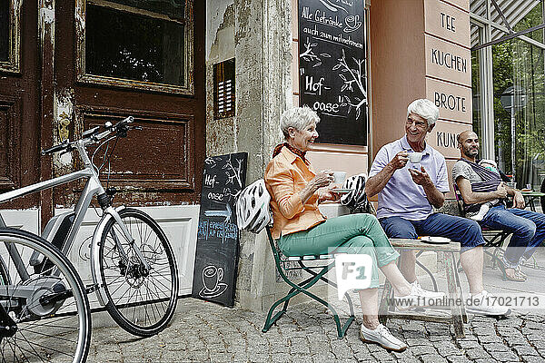 Tourists with electric bicycle drinking coffee while sitting at old town of Dresden  Germany