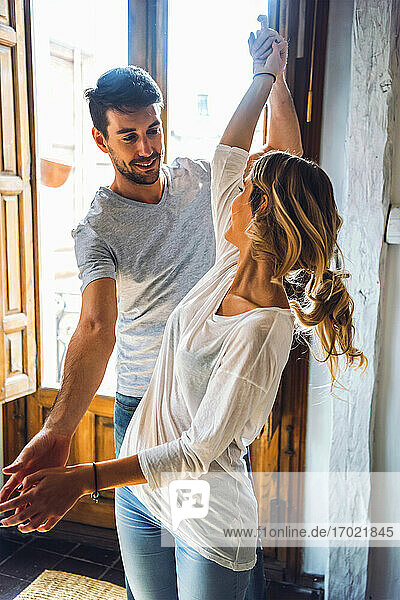 Young couple dancing at the window at home