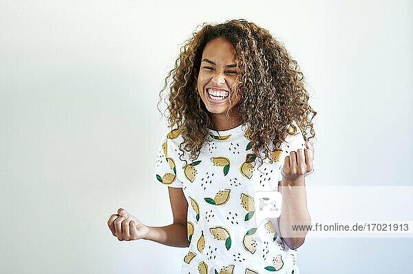 Glückliche afro-junge Frau triumphiert gestikulierend gegen eine weiße Wand Glückliche afro-junge Frau triumphiert gestikulierend gegen eine weiße Wand