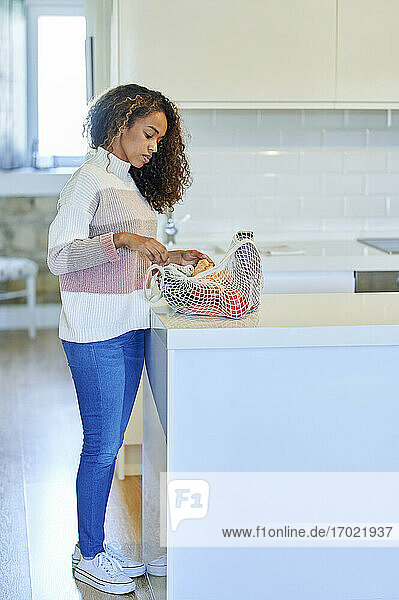 Young woman with curly hair checking groceries on kitchen counter at home