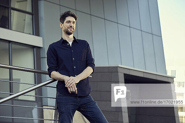 Confident businessman smiling while leaning on railing