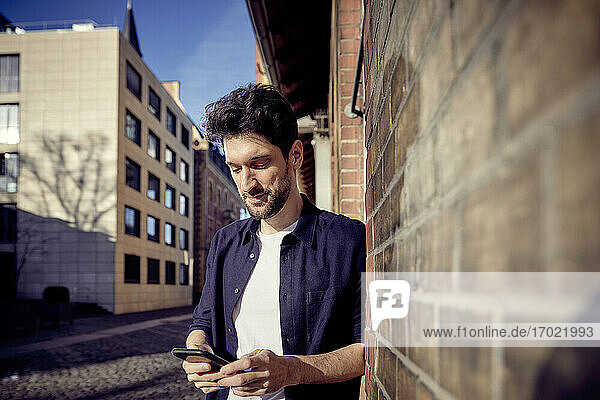 Businessman using mobile phone while leaning on wall in city