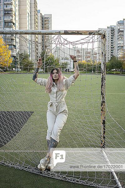 Hipster-Frau lehnt am Netz eines Fußballtors in der Stadt Hipster-Frau lehnt am Netz eines Fußballtors in der Stadt