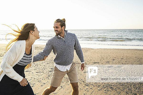 Fröhliches junges Paar  das sich an einem sonnigen Tag am Strand vergnügt Fröhliches junges Paar, das sich an einem sonnigen Tag am Strand vergnügt