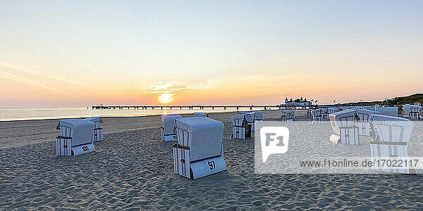 Germany  Mecklenburg-Western Pomerania  Ahlbeck  Hooded beach chairs on sandy coastal beach at sunrise