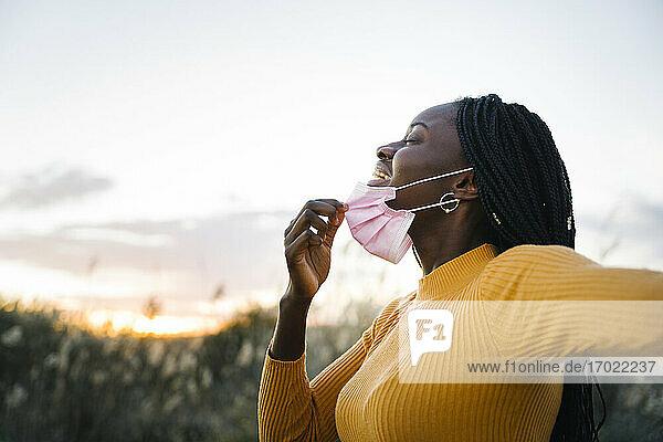 Glückliches Teenager-Mädchen mit geschlossenen Augen  das seine Maske abnimmt und in einem Feld bei Sonnenuntergang inhaliert