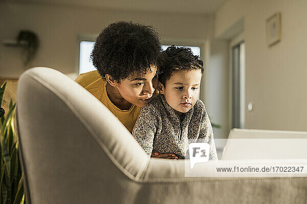 Young woman and boy using digital tablet while sitting on sofa at home